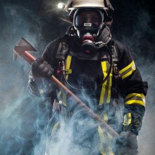 Stephan, Teil der Freiwilligen Feuerwehr Erlensee Rückingen posiert beim Feuerwehr-Kalendershooting im Rauch mit Schutzkleidung und Axt